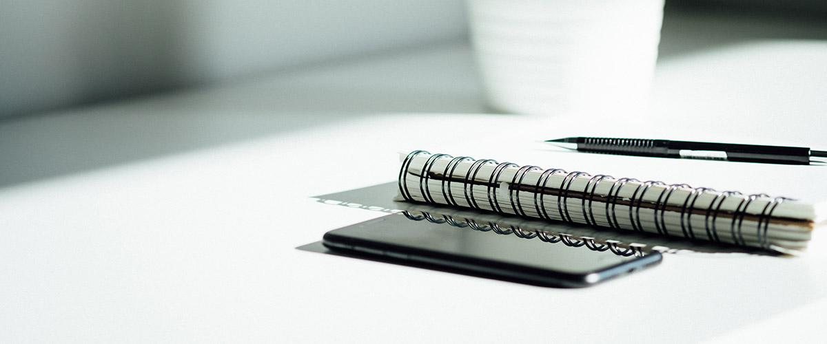 Photo byDose MediaonUnsplash of a notebook and pen